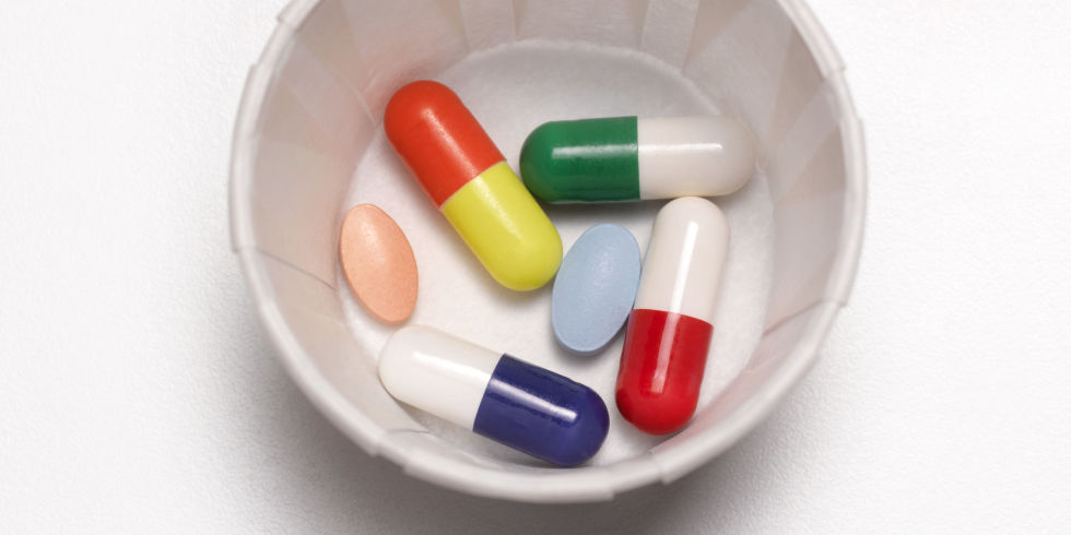 Pills and tablets and antibiotics in a paper cup