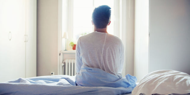 Man sitting in bed in morning waking up