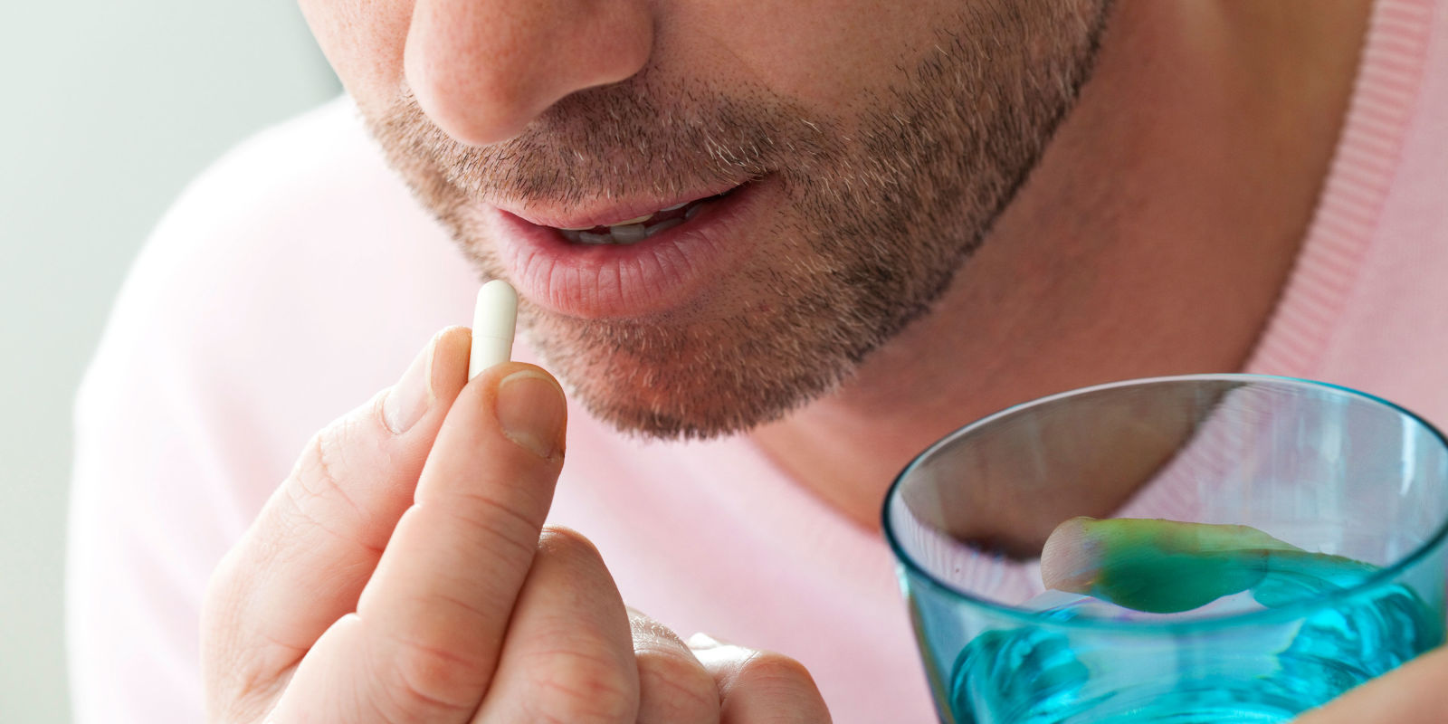 man in pink shirt taking pill medicine with water - Morning After Pill Time Frame