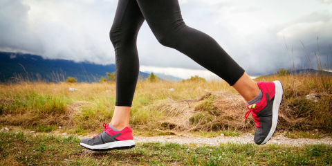 Macro of woman legs in sport shoes, running over the wild terrain, under the cloudy sky