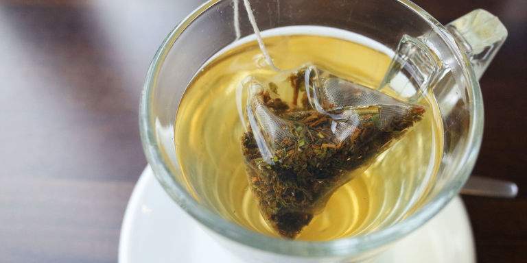High Angle View Of Green Tea Bag In Cup On Table