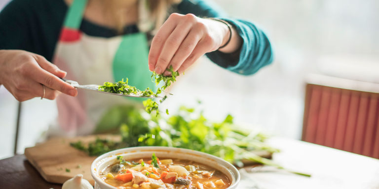 A woman wearing an apron, sitting at a table, sprinkling herbs into a bowl of vegetable stew