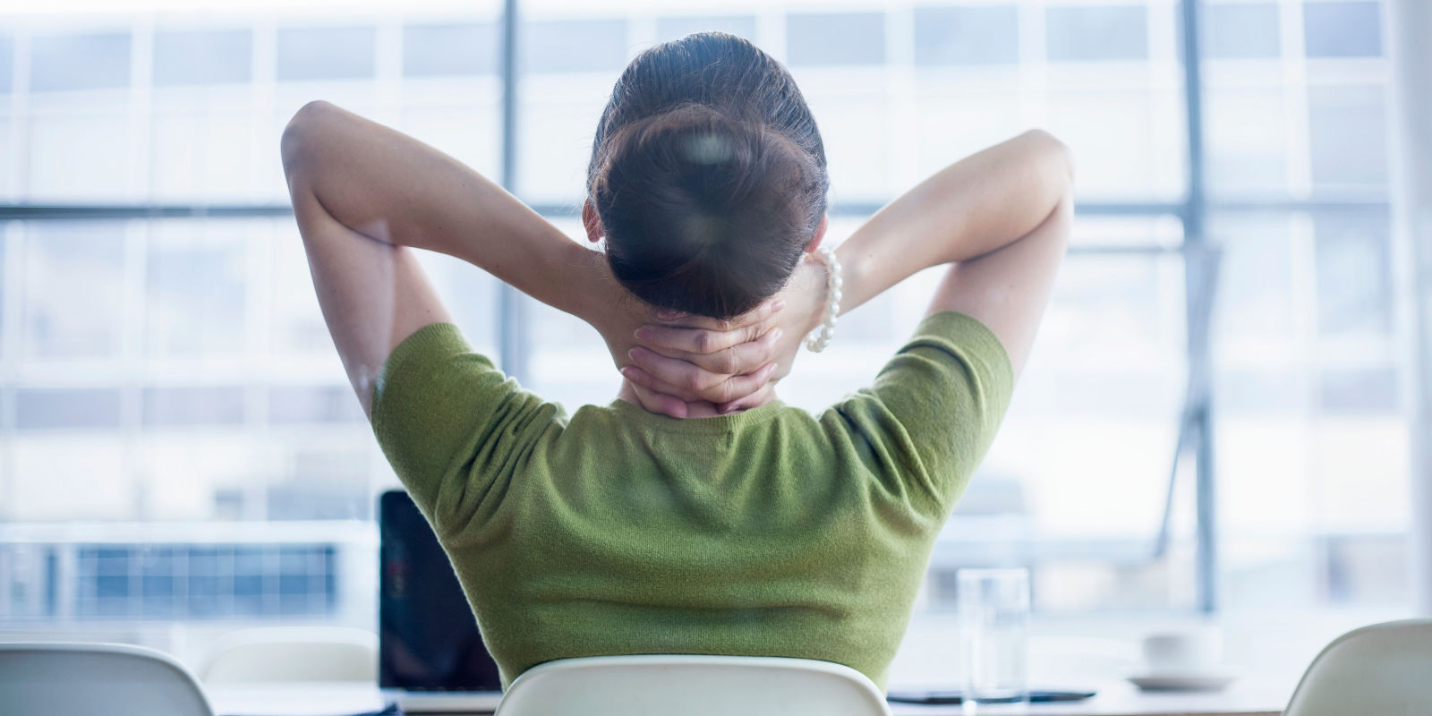 Woman Sitting At Desk With Sore Neck