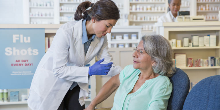 Pharmacist giving pensioner flu vaccine