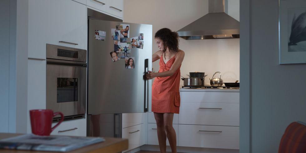 Woman looking in fridge at night