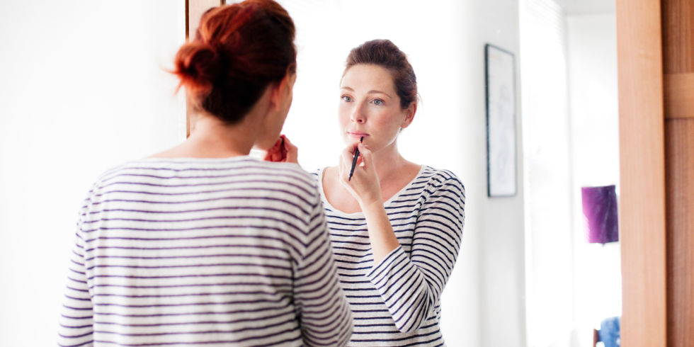 Woman applying makeup lipstick in the mirror