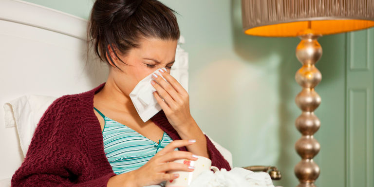 Woman in bed with a cold holding tissue to her face