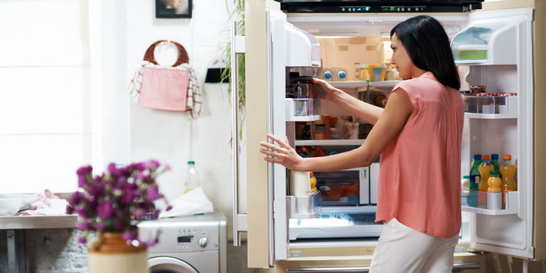 Woman opening fridge