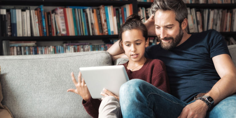 Father sat with daughter looking at tablet