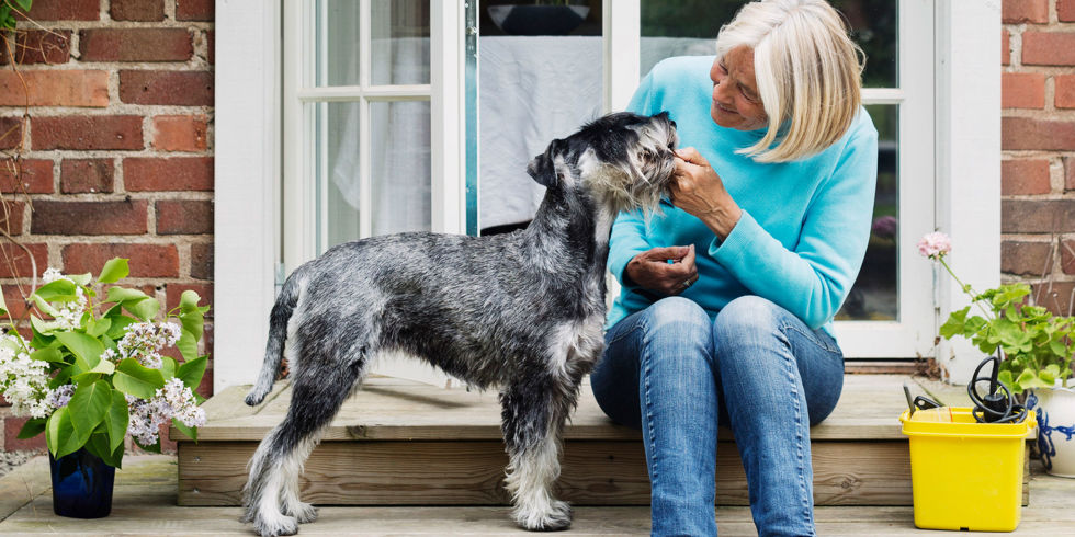 senior woman with dog at house entrance