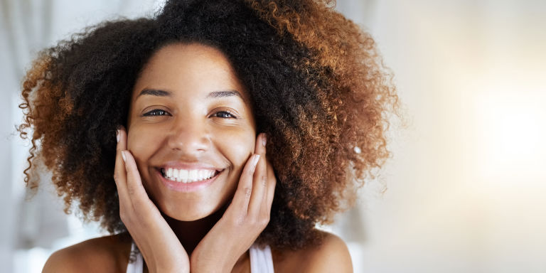 Smiling woman with good skin touching face