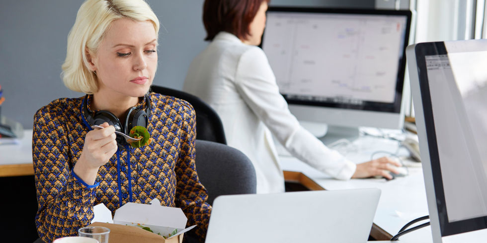 Female designer looking at laptop during working lunch at office desk