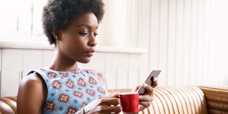 Woman looking at phone drinking coffee in cafe