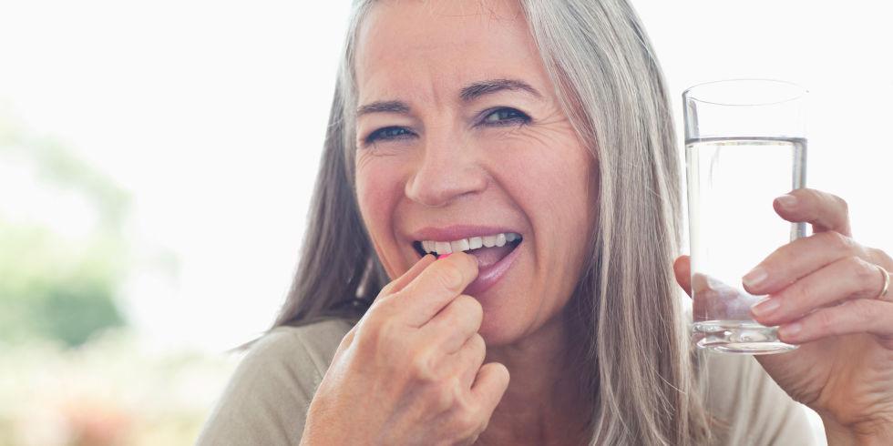 Woman taking vitamin d tablet